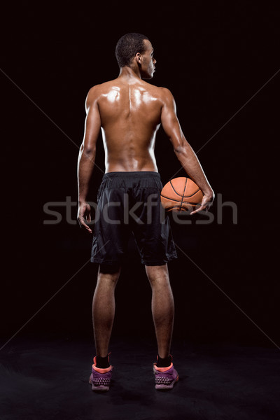 Stock photo: African american basketball player posing with ball on black