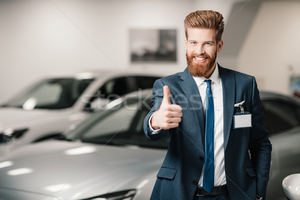 salesman in suit showing thumb up and looking at camera in dealership salon   Stock photo © LightFieldStudios