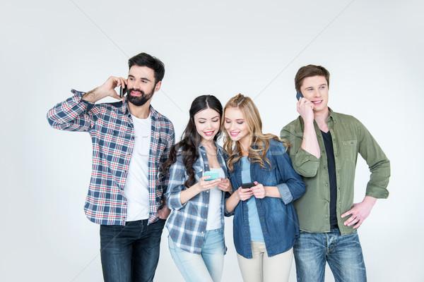 Quatre jeunes amis vêtements smartphones Photo stock © LightFieldStudios