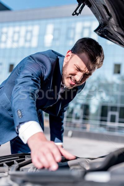 Stock photo: businessman repairing car