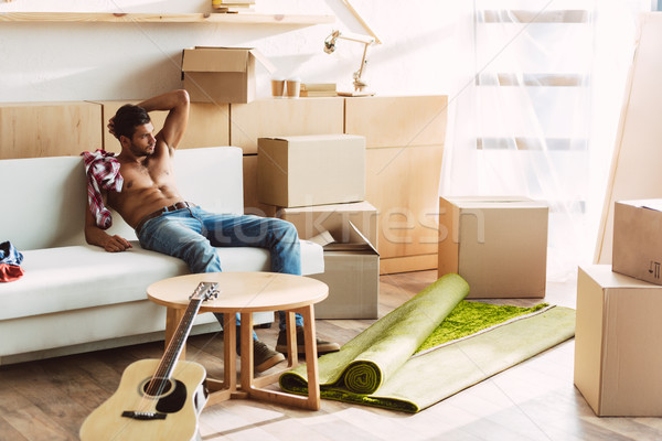 Póló nélkül férfi mozog új ház jóképű ül Stock fotó © LightFieldStudios