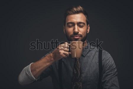 Handsome man smelling coffee Stock photo © LightFieldStudios