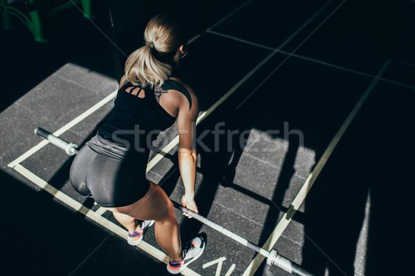 sportswoman lifting barbell in gym Stock photo © LightFieldStudios