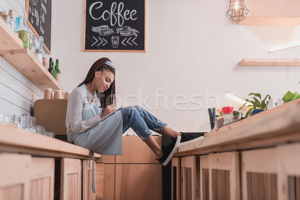 barista sitting on counter with notebook Stock photo © LightFieldStudios
