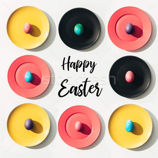 top view of easter eggs on colorful plates with Happy Easter lettering Stock photo © LightFieldStudios