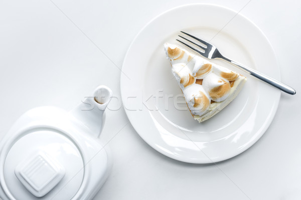 top view of teapot and delicious piece of cake with meringue on white table Stock photo © LightFieldStudios