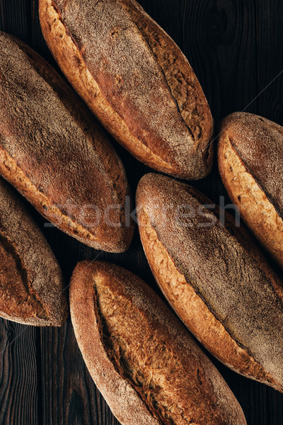 Stock photo: close up view of arranged loafs of bread on wooden surface