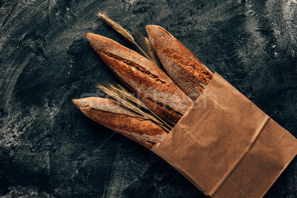 Stock photo: top view of arranged french baguettes in paper bag and wheat on dark tabletop with flour
