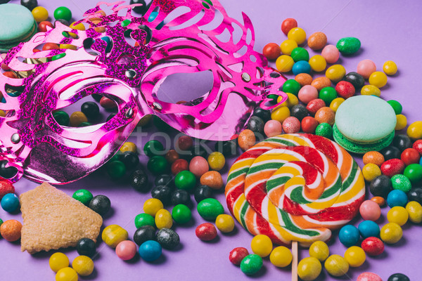 close up view of masquerade mask, lollipop and candies isolated on purple Stock photo © LightFieldStudios