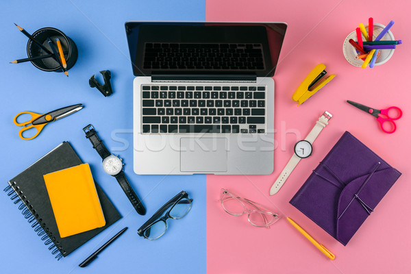 top view of laptop with blank screen, eyeglasses, wristwatches and notebooks divided at male and fem Stock photo © LightFieldStudios