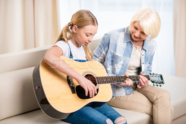 Smiling senior woman looking at preteen girl playing acoustic guitar on sofa Stock photo © LightFieldStudios
