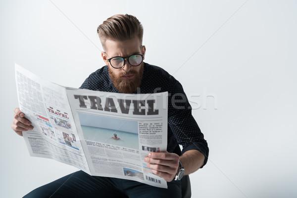 portrait of focused stylish man reading newspaper on white Stock photo © LightFieldStudios