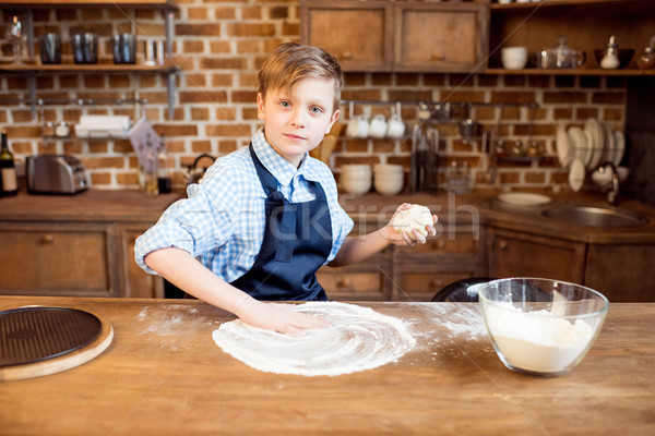 little boy making pizza dough on wooden tabletop in kitchen  Stock photo © LightFieldStudios