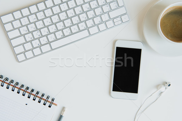 Top view of keyboard with office supplies and smartphone on table top. laptop desk coffee Stock photo © LightFieldStudios