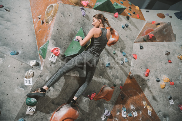 woman climbing wall with grips Stock photo © LightFieldStudios