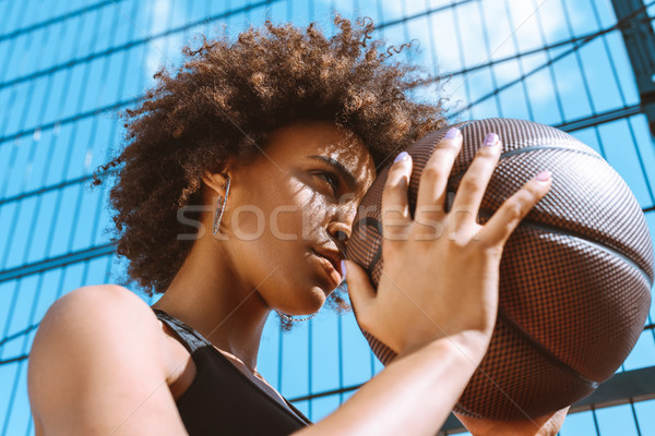 african-american woman adjusting aim with basketball Stock photo © LightFieldStudios