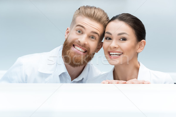 portrait of smiling scientists looking out behind table in lab Stock photo © LightFieldStudios