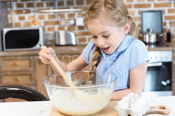Excited little girl with wooden spoon mixing dough in glass bowl Stock photo © LightFieldStudios
