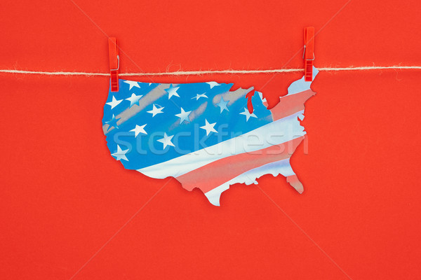 top view of piece of map with american flag hanging on rope isolated on red, presidents day concept Stock photo © LightFieldStudios