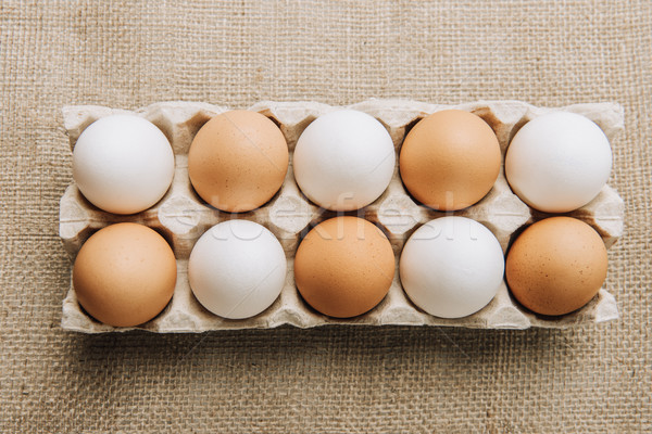 white and brown eggs laying in egg carton on sackcloth Stock photo © LightFieldStudios