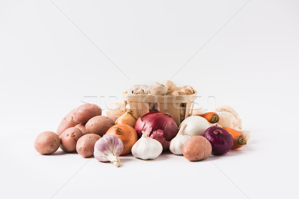 heap of mushrooms laying in basket over vegetables on white background   Stock photo © LightFieldStudios