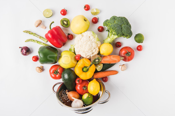 Flat lay composition of colorful vegetables and fruits in colander isolated on white background Stock photo © LightFieldStudios