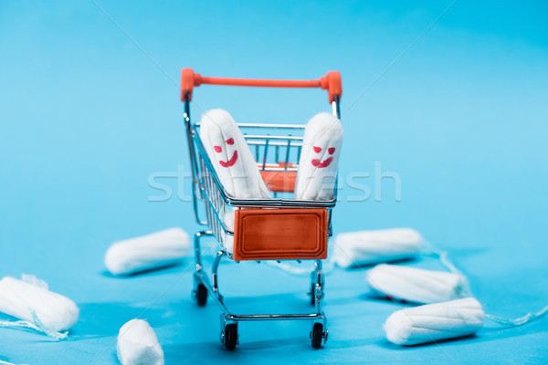 tampons with happy smileys in small shopping cart on blue Stock photo © LightFieldStudios