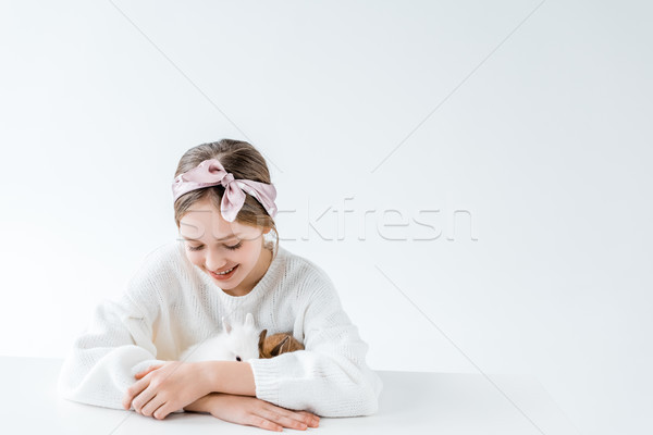beautiful happy girl playing with adorable furry rabbits on white  Stock photo © LightFieldStudios