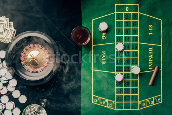 Casino table with roulette and glass with whiskey Stock photo © LightFieldStudios