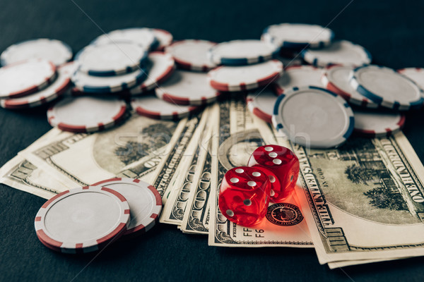Money with dice and chips on casino table Stock photo © LightFieldStudios