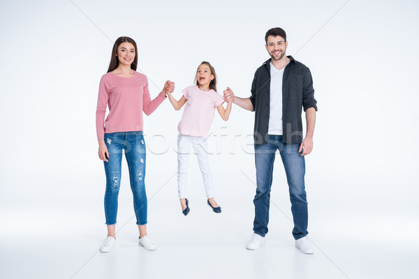 Happy young family with one child holding hands and smiling at camera  Stock photo © LightFieldStudios