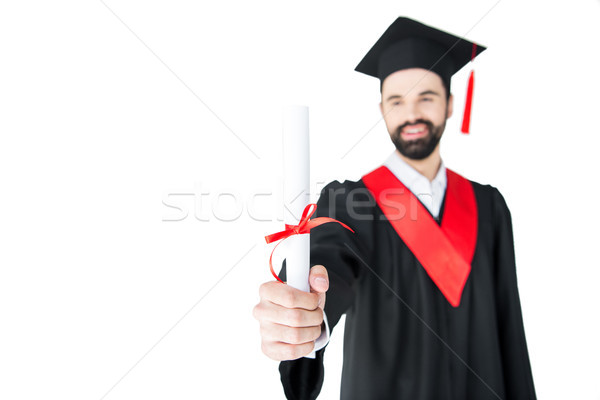 Smiling young man in graduation gown holding certificate Stock photo © LightFieldStudios