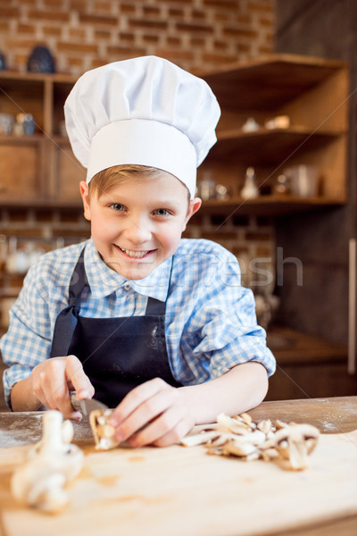 little boy in chef hat cutting mushrooms for pizza ingredients Stock photo © LightFieldStudios