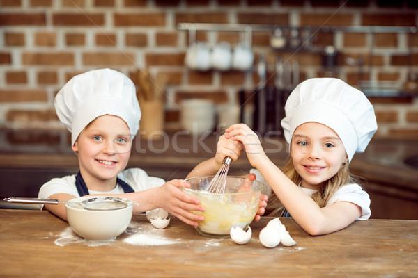 portrait of smiling kids in chef hats making dough for cookies Stock photo © LightFieldStudios