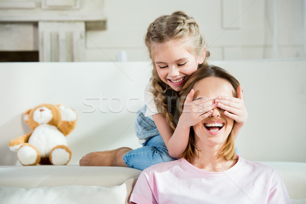 Happy mother and daughter having fun and playing at home Stock photo © LightFieldStudios