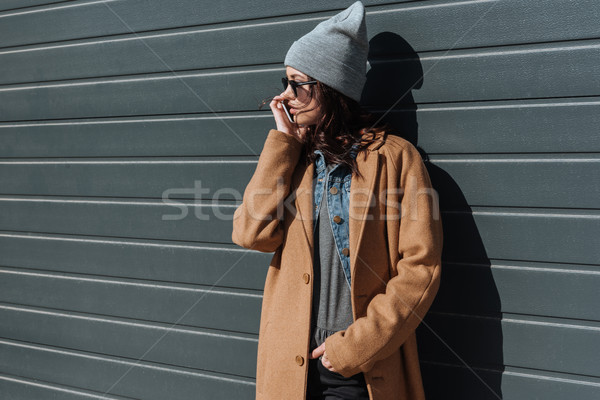 Woman in autumn outfit talking by smartphone Stock photo © LightFieldStudios