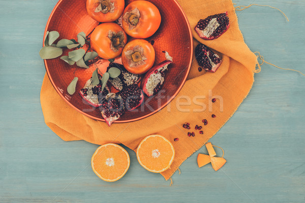 top view of persimmons with cut oranges and pomegranates on plate on orange tablecloth Stock photo © LightFieldStudios