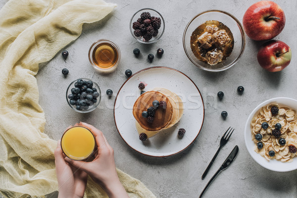top view of person eating healthy breakfast with homemade pancakes, fresh fruits and honey on grey  Stock photo © LightFieldStudios