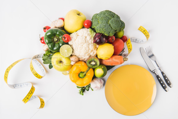 vegetables and fruits laying on white background with fork, spoon, measuring tape and plate Stock photo © LightFieldStudios