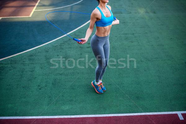 Athletic woman using jump rope Stock photo © LightFieldStudios