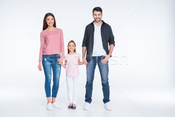 Happy young family with one child holding hands on white Stock photo © LightFieldStudios