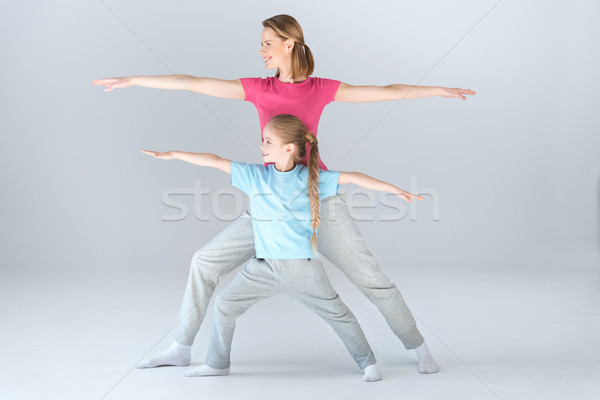 Side view of sporty mother and daughter practicing warrior yoga pose together on white Stock photo © LightFieldStudios