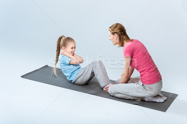 high angle view of sporty mother and daughter exercising on mats together on white Stock photo © LightFieldStudios