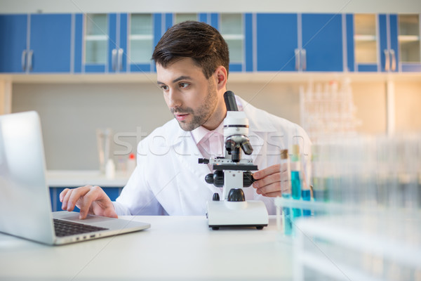 Man scientist in lab coat working with microscope and laptop Stock photo © LightFieldStudios