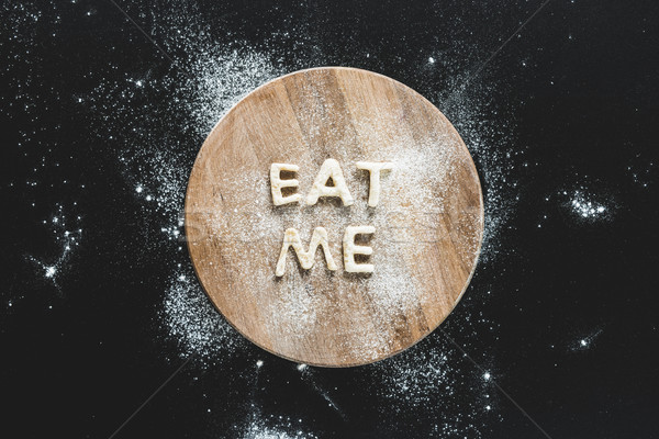 Top view of edible lettering eat me from dough on wooden cutting board, baking cookies concept Stock photo © LightFieldStudios