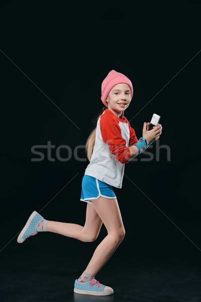 girl in sportswear running and using smartphone isolated on black. 12 year old kids concept Stock photo © LightFieldStudios