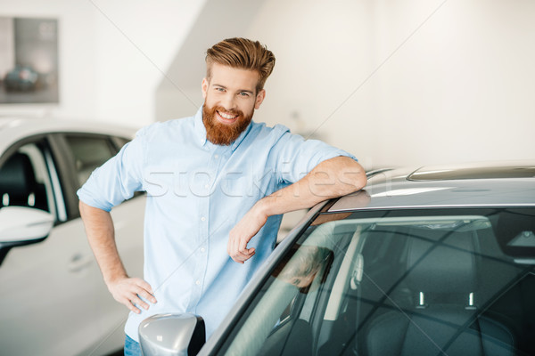 Handsome bearded young man standing with new car in auto salon Stock photo © LightFieldStudios