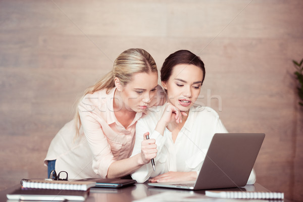 Young concentrated businesswomen looking at laptop Stock photo © LightFieldStudios