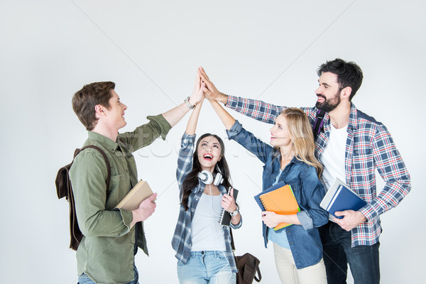 Stock photo: four young students in casual clothes holding books and giving highfive on white