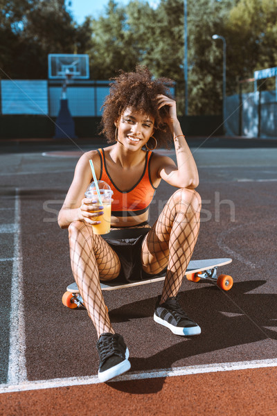 african-american woman on longboard with juice Stock photo © LightFieldStudios